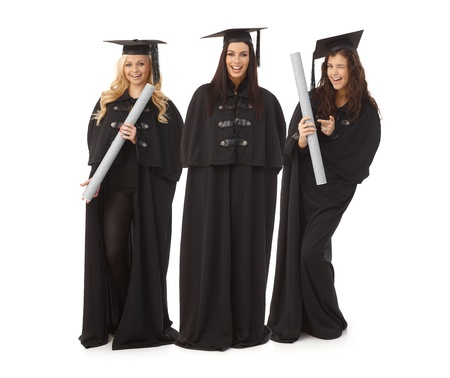 academic dress: Three pretty female graduates in academic dress smiling happy, holding diploma.