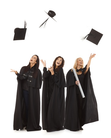 Three female graduates in academic dress throwing in the air square academic cap smiling happy. photo