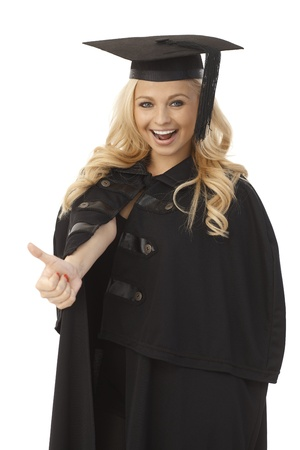 Happy female graduate in academic dress showing thumb-up sign.