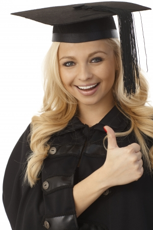 academic dress: Closeup photo of happy blonde female graduate showing thumb-up sign.