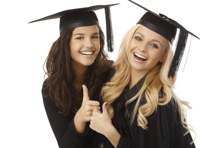 university sign: Beautiful young female graduates in square academic cap showing ok sign, hugging, smiling happy. Stock Photo