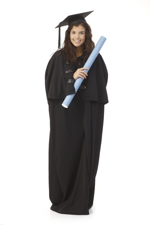 academic dress: Beautiful young female graduate in graduation gown and cap holding diploma, smiling happy.