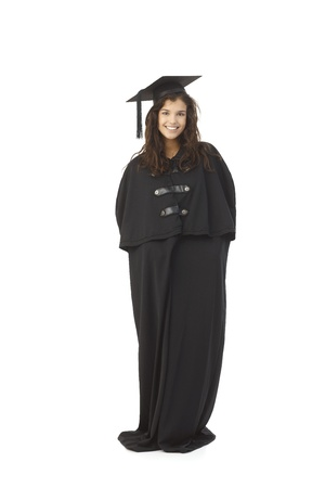 academic dress: Happy female graduate standing in full academic dress, smiling. Stock Photo