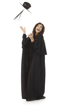 academic dress: Young female graduate throwing in the air square academic cap, smiling happy. Stock Photo