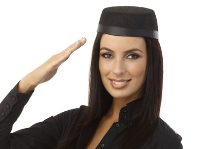 Closeup portrait of happy young attractive stewardess saluting, looking at camera. photo