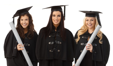 academic dress: Portrait of three attractive female graduates smiling happy in academic dress, holding diploma. Stock Photo