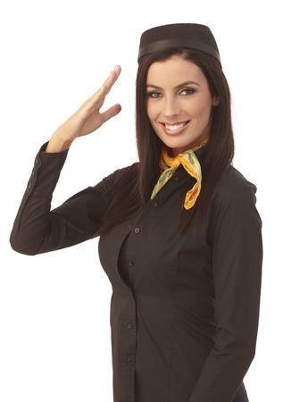 Pretty stewardess saluting, smiling happy. photo