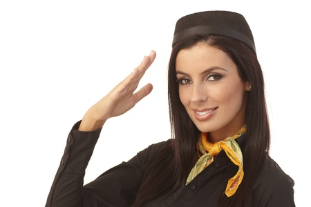 Closeup portrait of attractive young stewardess saluting, smiling, looking at camera. photo