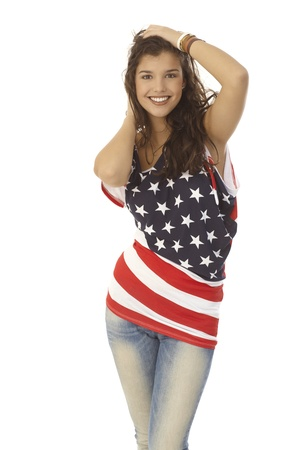 Beautiful young American woman in American flag t-shirt, posing, hand in hair, smiling, looking at camera. photo