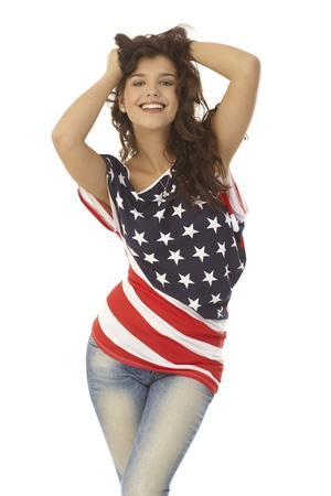 Sexy young American girl posing in American flag t-shirt, hand in hair, smiling happy. photo