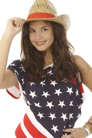 Closeup portrait of American beauty in American flag top and straw hat, smiling, looking at camera. photo