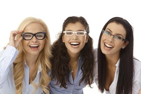 Close-up ritratto di belle giovani donne che indossano gli occhiali, sorridente felice, guardando a porte chiuse.