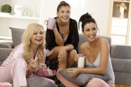 roommates: Girls together at home, watching tv in pyjamas, smiling happy.