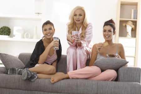 roommates: Female friends watching romantic movie at home on tv, all in pyjamas.