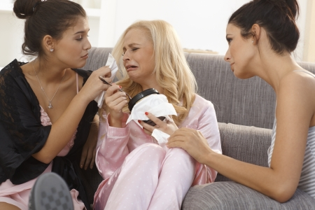 tears: Female friends comforting crying girl at home, wearing pyjamas, wiping tears. Stock Photo