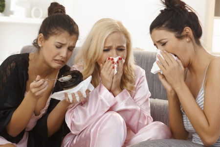 adult crying: Portrait of three crying women at home, sharing sorrow, wearing pyjamas.