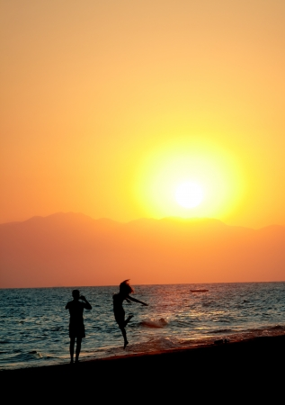 Silhouette of young couple having fun on beach at sunset photo