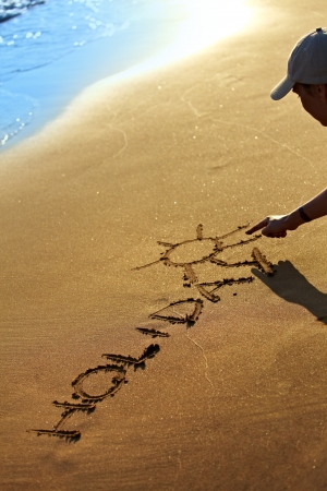sand writing: Someone writing holiday text in clean sand at summer. Focus placed on text. Stock Photo