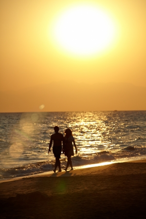 vertical image: Silhouette of romantic love couple walking on beach hand in hand at sunset.