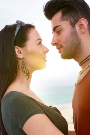 be kissed: Young loving couple kissing on the beach, side view.