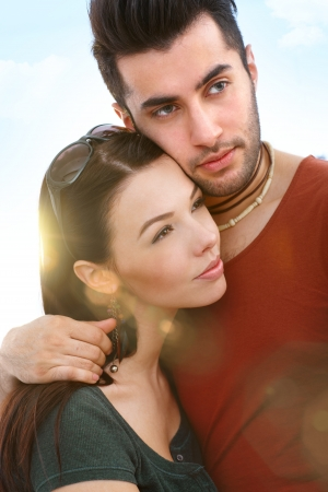 Outdoor portrait of young romantic couple embracing, looking away. photo