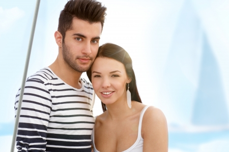 Summer portrait of attractive young loving couple on sailing boat. photo