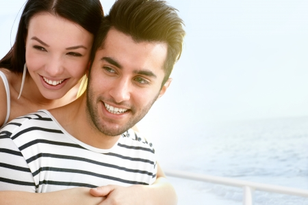 Happy young couple smiling, embracing on sailboat    photo