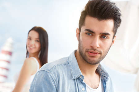 bristly: Outdoor portrait of handsome young guy, girl at background