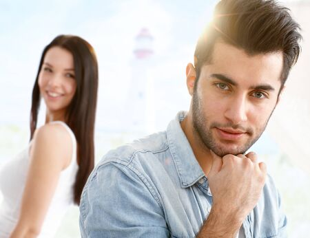 bristly: Outdoor portrait of goodlooking boy, girl at background looking back, flirting