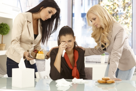 Young female office workers comforting crying colleague by cakes and doughnut. photo