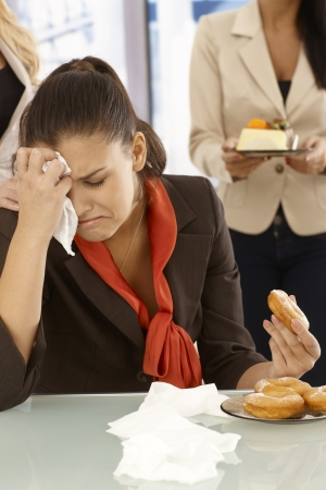 Unhappy office worker sitting at desk, crying, eating doughnut. photo