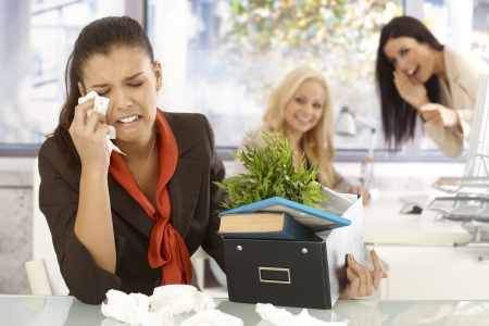 Fired young female office worker sitting at desk, crying, colleagues laughing at her at the background. Stock Photo