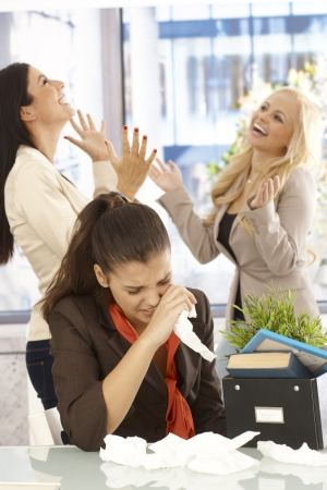 disgrace: Fired female employee crying at desk, colleagues celebrating at the background.