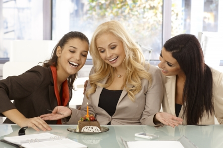 Young businesswomen celebrating birthday on workplace. Having chocolate cake with candle.