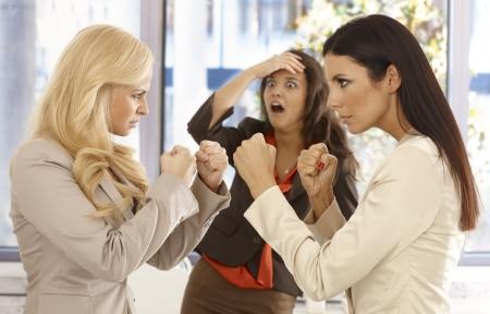 mujeres peleando: Decidida lucha empresarias en el lugar de trabajo, colega joven que mira con temor desde el fondo. Foto de archivo