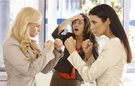 women fighting: Determined businesswomen fighting at workplace, young colleague watching it with fear from the background. Stock Photo