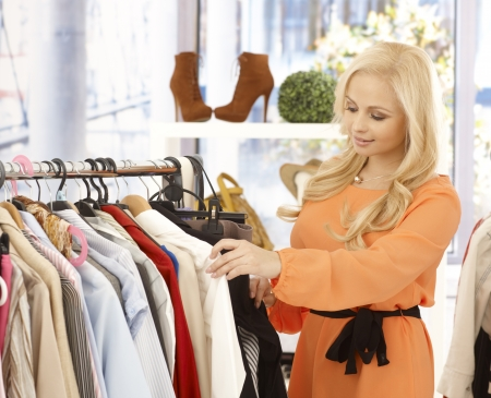 Attractive young blonde woman looking at clothes in shop. photo