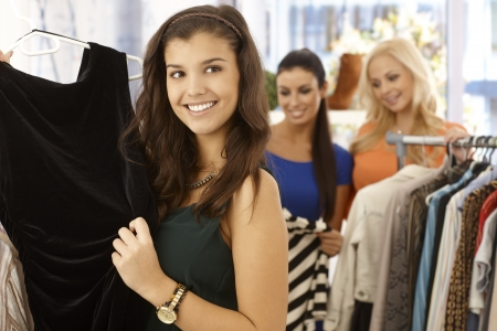 Pretty girl looking at black dress at clothes store smiling happy. Stock Photo - 18424851
