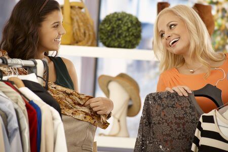 Female friends shopping together at clothes store, smiling happy. Stock Photo - 18424830