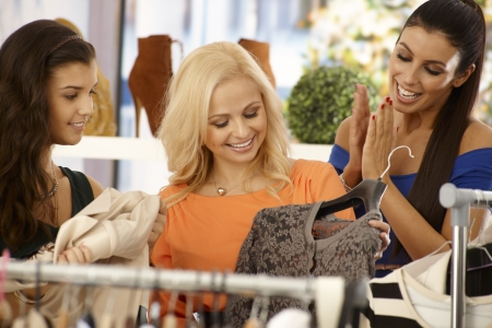 Happy young female friends shopping together at clothes store. photo