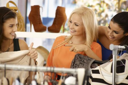 finding a mate: Young female friends shopping and searching among clothes at clothes store, smiling happy. Stock Photo