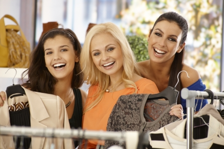Three girls shopping together at clothes store, smiling happy, looking at camera. Stock Photo - 18424855