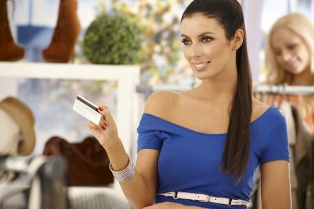 bankcard: Beautiful woman paying by credit card at clothes store, smiling.