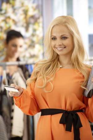 Attractive blonde woman paying by credit card at clothes store, smiling happy. Stock Photo - 18424850