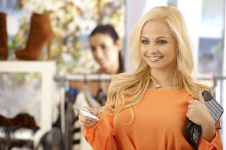 Beautiful elegant blonde female paying by credit card at clothes store, smiling happy. photo