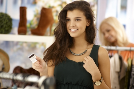 Attractive female paying by credit card at clothes store, smiling happy. photo