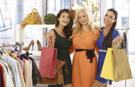 Three female friends standing at clothes store with shopping bags, smiling happy at camera.