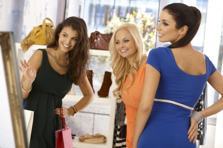 Pretty young girl trying on blue dress at clothes store, female friends looking at her, all smiling happy.