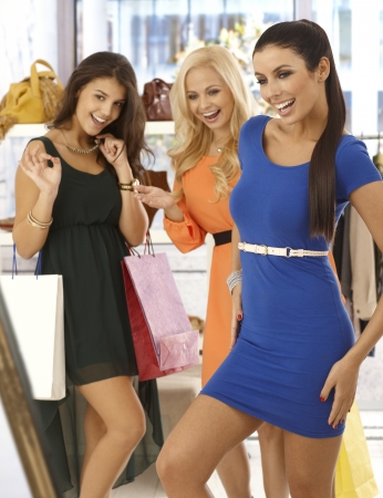 Happy girls shopping together, one trying on blue mini dress, friends looking at her with joy. photo