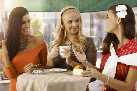 Feliz amigas con torta y caf�, charlando en el caf� al aire libre. photo